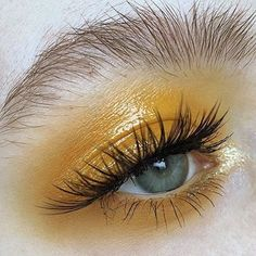 Yellow eye make up. Natural messy brows.