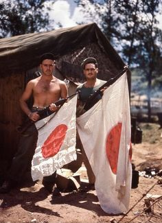Two Marines hoist freshly-captured Japanese flags on their M1 carbines somewhere in the Marianas.
