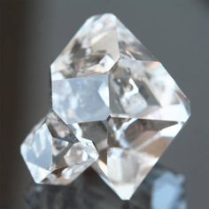 This large double terminated Herkimer Diamond quartz crystal has incredible clarity with beautiful natural facets, and a clear twin crystal attached to one side! The AAA collector stone from Herkimer, NY measures 20 x 19 x 16 mm, weighs 24 carats, and has an indented key crystal.