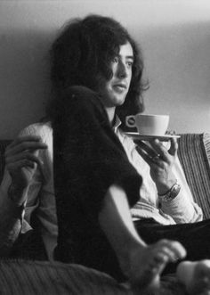"""""""  Jimmy Page sits barefoot (probably in a hotel room) with cup of tea during the band's second American tour, May 1969. """""""