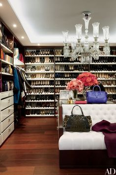 Jean-Louis Deniot–designed shelves line the dressing room of handbag designer Nancy Gonzalez's home in Colombia; the Baccarat chandelier dates from the 1880s, and the handbag and tote in the foreground are Gonzalez staples.