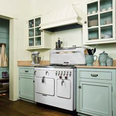 A pastel color scheme, vintage stove, and wood-plank floors give this cottage cookspace kitschy charm. | Photo: Jack Thompson | thisoldhouse.com
