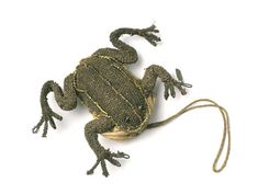 Small purse in the shape of a frog: 17th century It is made in two halves; the back is on a hard base with padding on top, the underside is on a more pliable base. The two are seamed together to just below the front legs and are lined with greenish-yellow silk with a gusset at each side to form a tiny purse with a drawstring fastening. The legs are made of wire and shaped with padding