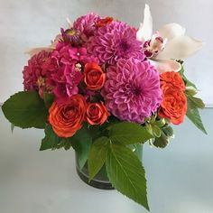 Hot pink ball dahlias, orange spray roses, cymbidium orchids, hot pink hydrangea and raspberry vine in a leaf wrapped glass cylinder.