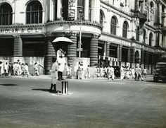 Street scene showing a traffic police standing with an umbrella in the centre on Chowringee Road in front of Whitewaw and Laidlaw & Co Ltd in the year Traffic Police, India Facts, Old Ads, India Travel, Kolkata, Past, Street View, Scene, Amazing
