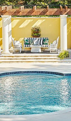 Just outside, the pool terrace by Hannah Seaton and Ed Castro encourages lounging and evening swims. Frontgate's armchairs and striped sofa shape a sitting area under the pergola. Ferns and potted plants thrive in the Atlanta sun. | Ed Castro for Atlanta Symphony Orchestra Show House 2015