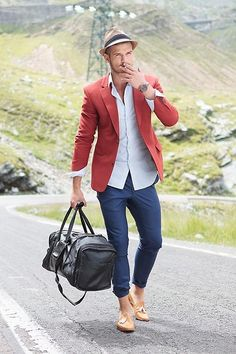 Matte red mens blazer, navy trousers, pale yellow shoes, black leather duffle bag.