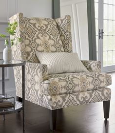 Our modern wing chair is a casual update on the traditional parlor chair, offering a stately refuge with its tall back and enveloping sides. Wrapped in an ikat-inspired motif inspired by an antique Indonesian robe, the Luxe chair showcases its neutral palette of cream, beige and gold on clean, contemporary lines. Solid maple legs finished in a black walnut finish complete the look. The Luxe Wing Chair is a Crate and Barrel exclusive.