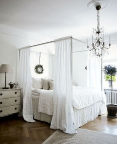 bedroom.  ikea four poster bed (?), swedish chest, white bedding, wreath.