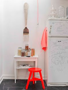 not crazy about the fork decor, but love the neon orange chair, and how it contrasts with the white
