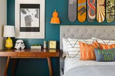 An array of fun, quirky accessories adorns a midcentury modern desk in this boy's bedroom. The fun doesn't stop there — colorful skateboards are mounted in a row above the bed, creating an unexpected and eye-catching form of artwork.