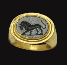 A ROMAN GOLD AND GREEN JASPER FINGER RING CIRCA 2ND CENTURY A.D. The plain hoop flat on the interior, rounded on the exterior, with a high oval stepped bezel, set with a flat oval stone engraved with a lion walking to the left, a bull's head in its mouth, on a groundline