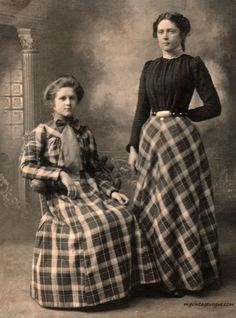 Two 1890s ladies, (sisters?) with matching plaid.  The standing lady's skirt is paired with a dark bodice.  The pattern is matched to flare away from the waistline over the hips.  The seated lady has a skirt cut on a different pattern and a matching bodice.  Her skirt looks like it has a gore in front so that the plaid pattern lays flat.  I can't quite tell what's going on in the bodice- straight sleeves, a rounded yoke and a large contrasting collar/ stock.  Image from My Vintage Visions…