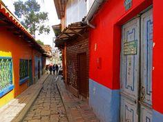 17. Colores rojos y amarillos en casas que forman una calle por la que nunca para el tráfico de personas.