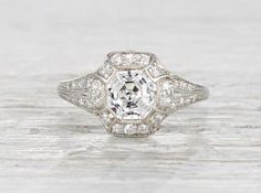 Antique Art Deco engagement ring made in platinum and centered with a GIA certified 1.22 carat old European cut diamond with H color and SI1 clarity. Accented with old European cut diamonds and black