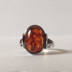 Beautiful size N Amber ring, sterling silver 925 hall marked. I believe it to be between 1970s & 1980s. Lovely unusual rainbow type patten to the side of the ring. 50p used to show size of ring. This is a vintage piece so has been worn. Please see pictures Any questions please ask