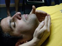My model -Mike - I am activating his thyroid gland in front of neck. Each hand position activates a gland of the endocrine or immune system. Energy is also run into the bone marrow as we place our hands over joints and bones.   Clear your energy system blockages with the 15 chakra aura healing session and have more energy. - http://aurachakrahealing.com/