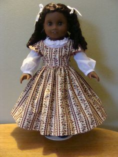 Civil War style outfit for 18 inch doll. The overdress is a floral striped cotton print. The bodice is trimmed with piping. The dress opens in