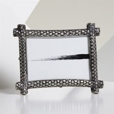 Made from brass and painted with nickel coloring, this Natori picture frame with embossed dragon scale motif is an interesting way to display your favorite photos.