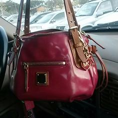 Dooney & Bourke small cute bag Patent Leather shoulder strap handbag red lining inside one open pocket inside and one zipper pocket inside of bag no tear has some minor wear of use no stains on the inside lining it does need some cleaning i dont know the measurments. it has long leather key holder  (MK keychain not included) Dooney & Bourke Bags Shoulder Bags