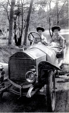 Two Hangyoku (Young Geisha) sitting in an early Automobile. The car is a Colibri (Hummingbird) manufactured by the Norddeutsche Automobil-Werke between 1908 and 1912.