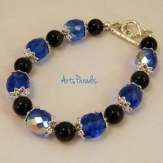 All Over - Black & Blue Bracelet This bracelet will not bruise your arm, promise! A wonderful blend of fire polished Czech glass beads and beautiful black cat's eye beads. Accented with bright silver bead caps and toggle clasp. A stunning piece for your winter wardrobe.