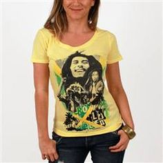 This yellow Catch A Fire Women's Fashion Top features multiple photos of Bob Marley with parts of the Jamaican flag visible behind. The words Bob Marley Irie Livin are found in colored blocks below with palm trees for a tropical look.