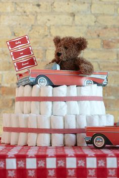 Diner-Themed Diaper Cake. Two-tiered diaper cake with 100 HUGGIES® Little Snugglers Diapers with diner accents,  ribbon and topped with a teddy bear.