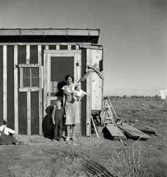 """December 1935. """"Resettled at Bosque Farms project in New Mexico. Family of four from Taos Junction shows temporary dwelling."""" Medium-format negative by Dorothea Lange for the Resettlement Administration."""