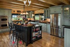 30 Rustic Kitchens Designed by Top Interior Designers Beautiful kitchen with island.  Love the glass cabinet doors.  #kitchens #kitchendesigns  homechanneltv.com<br> View rustic kitchens designed by the best rustic interior designers. From farmhouse kitchens to log homes and cabins with rustic kitchen ideas & tips.