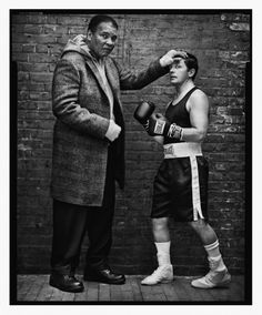 """Ali and Michael J. Fox, New York City, 2004  -  Mark Seliger: """"After the shoot, the champ was signing a Neil Leifer print of his legendary fight with Sonny Liston that I have hanging in my house. He wrote, 'Love is the net where hearts are caught like fish' across the bottom of the print, and when he made a mistake, he would fix it by inking in the miswritten letter with a big black heart.""""   -  Mark Seliger is a renowned portrait photographer."""