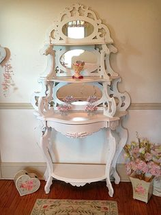 This beautifully hand carved etagere is a masterpiece of elegance. This lovely piece has three tiers of display shelves with stunning oval mirrors, a hidden drawer and a bottom shelf. It has been refinished a linen white and lightly distressed.