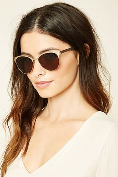 A pair of metal cat eye sunglasses featuring a high-polish frame and…