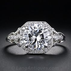 A superb 2.17 carat round brilliant-cut diamond - accompanied by a GIA Gem Trade Laboratory grading report stating D color, VS2 clarity is framed by small sparkling accent diamonds atop a fancy scroll motif gallery and openwork foliate motif diamond-set shoulders. The style of this gorgeous modern platinum and diamond ring pays homage to the classic flowing designs of the Edwardian period at the beginning of the twentieth century. A timeless beauty ... Ring size 6 1/2.