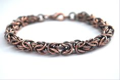 Over 130 copper rings are handwoven in the Byzantine pattern to form a weighty, substantial bracelet. Oxidized, then tumbled to a shine, and finished with a lobster claw clasp. Length is approximately 8 inches (20 cm) long.