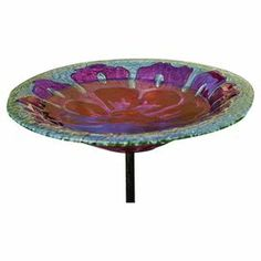"Invite feathered friends to your garden with this beautiful birdbath and metal stand, artfully crafted of glass and showcasing a pink flower motif.  Product: BirdbathConstruction Material: Metal and glassColor: Green, purple and redFeatures: Includes two-piece stand with a three prong ground stakeDimensions: 24.75"" H x 11.25"" Diameter"