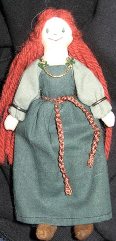 An ordinary cloth doll I bought from someone that I turned into a Viking lady with a few accessories, namely the brooches (old 14K post earrings), armrings (old sterling silver hoop earrings), the chain (a piece of gold piping), and shoes (made by me with thin suede).