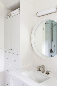 Light gray shaker linen cabinets fitted with an overhead shelf are positioned beside a light gray washstand topped with a white quartz countertop holding a rectangular sink and modern satin nickel faucet beneath a round convex marble vanity mirror lit by a long white glass sconce.