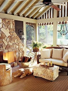 A large stone fireplace is the centerpiece to this screened porch that sits in a wood cabin along Lake Michigan. Fire logs are nestled in a silver drink tub next to a slipcovered ottoman with a floral and fruity pattern. Vaulted wooden ceiling beams are j