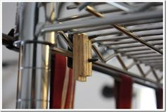 Use a scrap piece of wood to attach a curtain rod to metal shelving. The curtain will hide all the ugly things stored on the shelves.