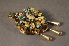 Victorian mourning locket in 14K yellow and rose gold, set with turquoises and seed pearls, two sterling silver  love birds have garnet eyes; crca 1890.