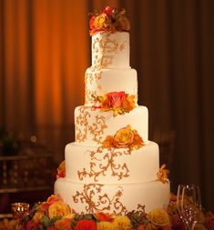 A tall floral fall-inspired wedding cake. See more amazing wedding cakes: https://www.insideweddings.com/news/planning-design/10-towering-cakes-that-amaze/1279/.  Photograph by: Ira Lippke Photography