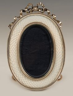 A Faberge silver and guilloche enamel oval frame, workmaster Andrei Gorianov, St Petersburg, circa 1908-1917. Of oval form, the surface decorated in translucent white enamel over a wavy engine-turned ground, the frame surmounted by an undulating silver bowknot.