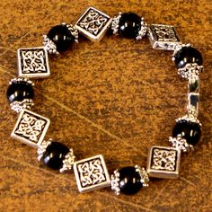 Black Celtic Bracelet  Everyday occasions still call for a touch of style. Semi-precious stones alternate with silver-tone Celtic-inspired beadwork on this stretch bracelet. Matching earrings also available.  Order yours!  #CreativeIrishGifts #Irish #Ireland