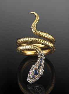Victorian Sapphire and Diamond Coiled Snake Ring  A finely scaled yellow gold coil forms the tail and body of a snake with a jeweled sapphire and diamond head set in silver top yellow gold.