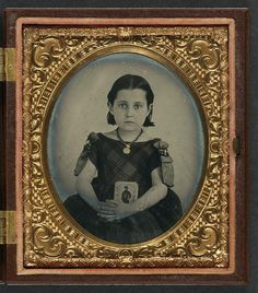 girl in mourning dress holding framed photograph of her father as a cavalryman with sword and Hardee hat