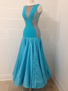 "Unique turquoise standard or smooth dress. Bodice is made from crepe with mesh and plunging back. Satin Chiffon skirt over organza. Heavily decorated with Swarovski crystals. Best for sizes from 4-8 and heights from 5'6"" to 5'10"" Gown by DSI London"