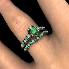 Boulevard ring with Emerald center stone, and diamond and emerald accent stones in 14K white gold with matching band.