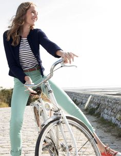 Fashion style by bicycle. Mint pants and striped shirt plus a white bicycle for a crisp and beachy look.