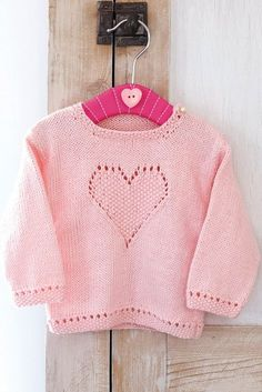 This adorable jumper for a baby is knitted in stocking stitch with moss-stitch edgings and a heart motif outlined with lace eyelets that creates a beautiful effect
